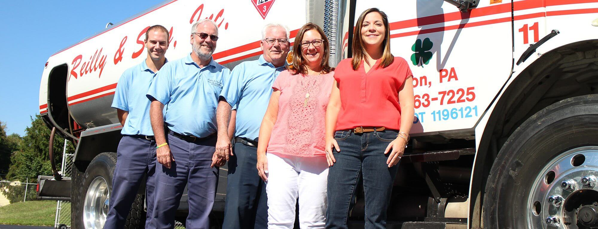 Reilly and Sons team standing in front of one of the trucks.